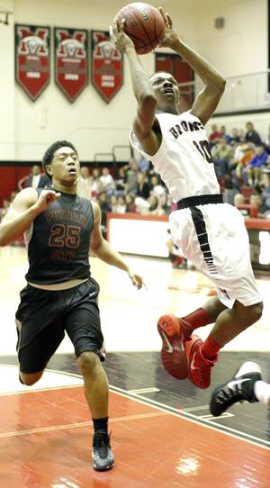 Photo - Mustang's Terrell Williams, right, goes to the basket in front of Putnam City's Chris Pogi.