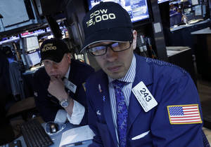 "Photo - Specialists Devin Cryan, left, and  Gabriel Freytes wear a ""Dow 15,000"" hats as they work at a post on the floor of the New York Stock Exchange Friday. AP Photo <strong>Richard Drew - AP</strong>"