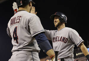 Photo - Cleveland Indians' Ryan Raburn, right, slaps hands with Mike Avilies after Raburn scored on an error by Minnesota Twins' first baseman Chris Colabello during the fourth inning of a baseball game, Thursday, Sept. 26, 2013, in Minneapolis.  (AP Photo/Jim Mone)
