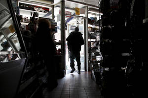 Photo -   A customer shops at Andy's Deli in the dark, Wednesday, Oct. 31, 2012, in New York. Days after superstorm Sandy hit, businesses both big and small are facing a tough choice, to reopen or stay closed. (AP Photo/Seth Wenig)