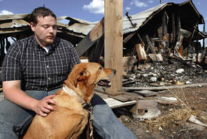 photo - Walt Harmon, 24, sits with his dog, Pal, a mutt, at the back of what&#039;s left of his family&#039;s home Tuesday afternoon, July 19, 2011. The dog awakened Walt&#039;s mother,  Susan Harmon with constant barking Sunday night when their home caught fire. Walt credits the pet with saving his life and allowing him to rescue his mother, and her parents, Harold and Donna Gilliam.  from the smoke-filled home before it was destroyed by flames.   The home is in rural Lincoln County about six miles north of Jacktown.     Photo by Jim Beckel, The Oklahoman