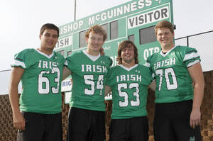 "Photo - HIGH SCHOOL FOOTBALL: Jonathan Olay, left, Andrew Williams, Luke Raczkowski and Dan Christiansen, members of the Bishop McGuinness offensive line, which call themselves ""The Million Dollar Line, pose at their football field in Oklahoma City, OK, Monday, June 17, 2013,  Photo by Paul Hellstern, The Oklahoman"