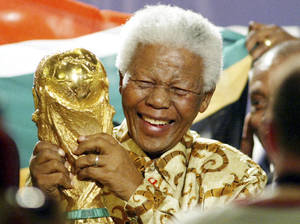 Photo - FILE - In this May 15, 2004 file photo, former South African President Nelson Mandela lifts the World Cup trophy in Zurich, Switzerland, after FIFA's executive committee announced that South Africa would host the 2010 FIFA World Cup soccer tournament. Mandela was pivotal in helping the country win the right to host the tournament. South Africa's President Jacob Zuma said, Thursday, Dec. 5, 2013, that Mandela has died. He was 95. (AP Photo/Michael Probst, File)