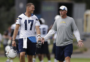 Photo - San Diego Chargers quarterback Philip Rivers (17) talks with offensive coordinator Ken Whisenhunt, right, during NFL football training camp Friday, July 26, 2013, in San Diego. (AP Photo/Gregory Bull)
