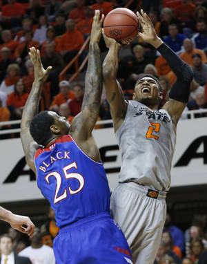 Photo - Oklahoma State wing Le'Bryan Nash (2) shoots in front of Kansas forward Tarik Black (25) during the second half of an NCAA college basketball game in Stillwater, Okla., Saturday, March 1, 2014. Oklahoma State won 72-65. (AP Photo/Sue Ogrocki)