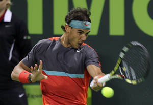 Photo - Spain's Rafael Nadal returns the ball to Germany's Peter Gojowczyk in their semifinal match the Qatar Open tennis tournament at the Khalifa Tennis Complex in Doha, Qatar, Friday, Jan. 3, 2014. (AP Photo/Osama Faisal)