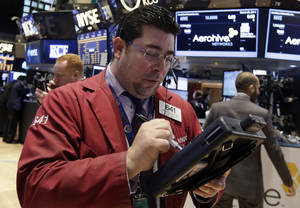 Photo - Trader Michael Capolino, center, works on the floor of the New York Stock Exchange Friday, March 28, 2014. After two days of declines, stocks were moving higher in early trading Friday following news that U.S. consumer spending rose the most in three months in February. (AP Photo/Richard Drew)