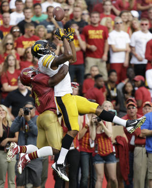 Photo - Iowa State defensive back Sam E. Richardson, left, breaks up a pass intended for Iowa wide receiver Tevaun Smith during the first half of an NCAA college football game, Saturday, Sept. 14, 2013, in Ames, Iowa. (AP Photo/Charlie Neibergall)