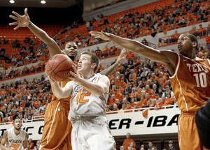 Photo - Oklahoma State's Keiton Page goes between Texas' Jaylen Bond, left, and Jonathan Holmes on Saturday in Stillwater. Oklahoma State won 90-78. Photo by Bryan Terry, The Oklahoman