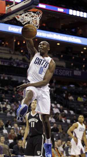 photo - Charlotte Bobcats' Bismack Biyombo (0) dunks past Brooklyn Nets' Brook Lopez (11) during the first half of an NBA basketball game in Charlotte, N.C., Wednesday, March 6, 2013. (AP Photo/Bob Leverone)
