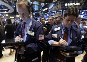 Photo - FILE - In this Friday, Jan. 17, 2014, file photo, traders Michael Smyth, left, and Patrick McKeon, work on the floor of the New York Stock Exchange. (AP Photo/Richard Drew, File)