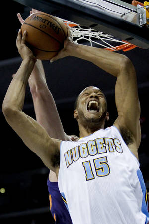 Photo - Denver Nuggets' Anthony Randolph (15) is fouled by Phoenix Suns' Miles Plumlee during the first quarter of an NBA basketball preseason game Wednesday, Oct. 23, 2013, in Denver. (AP Photo/Barry Gutierrez)