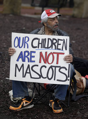 Photo - Jerald Beckman holds up a sign in protest of the use of Chief Wahoo by the Cleveland  Indians before a baseball game between the Minnesota Twins and the Cleveland Indians, Friday, April 4, 2014, in Cleveland. (AP Photo/Tony Dejak)