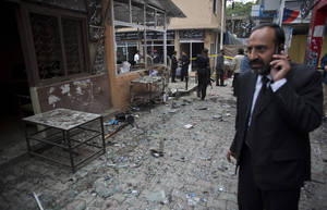 Photo - A Pakistani lawyer talks on his mobile phone at the site of a suicide attack in a court complex, Monday, March 3, 2014 in Islamabad, Pakistan. Two suicide bombers blew themselves up at the complex on Monday, killing nearly a dozen and wounding scores in a rare terror attack in the heart of Islamabad, officials said. (AP Photo/B.K. Bangash)