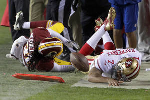 Photo - Washington Redskins strong safety Brandon Meriweather collides with San Francisco 49ers quarterback Colin Kaepernick as they slide out-of-bounds during the second half of an NFL football game in Landover, Md., Monday, Nov. 25, 2013. The 49ers defeated the Redskins 27-6. (AP Photo/Mark Tenally)