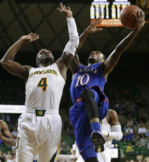 Photo - Baylor guard Gary Franklin (4) defends against a shot by Kansas' Naadir Tharpe (10) in the first half of an NCAA college basketball game, Tuesday, Feb. 4, 2014, in Waco, Texas. (AP Photo/Tony Gutierrez)