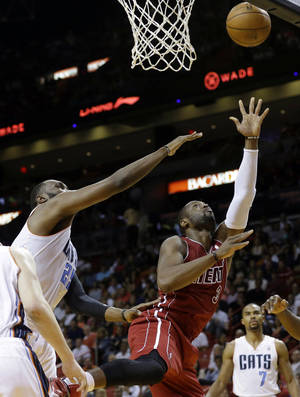 Photo - Miami Heat's Dwyane Wade (3) shoots over Charlotte Bobcats' Al Jefferson, left, during the first half of an NBA basketball game Sunday, Dec. 1, 2013, in Miami. (AP Photo/Lynne Sladky)