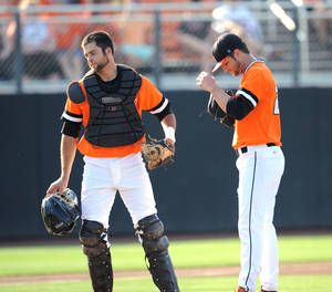 Photo - Oklahoma State catcher Bryan Case, left, walks back to his position after talking with Tyler Nurdin, right, his pitcher during the first inning of an NCAA college baseball regional tournament game in Stillwater, OK, Sunday, June 1, 2014. (AP Photo/Brody Schmidt)