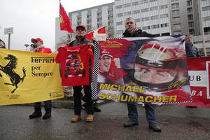 Photo - Fans of Michael Schumacher hold banners to honor the Formula One Champion on his 45th birthday, Friday Jan. 3, 2014, in front of the Grenoble hospital where former seven-time Formula One champion Michael Schumacher is being treated after sustaining a head injury during a ski accident. Schumacher has been in a medically induced coma since Sunday, when he struck his head on a rock while on a family vacation. (AP Photo/Thibault Camus)