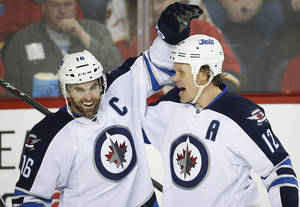 Photo - Winnipeg Jets' Olli Jokinen, right, from Finland, celebrates his goal with teammate Andrew Ladd during second period NHL hockey action against the Calgary Flames in Calgary, Canada, Thursday, Jan. 16, 2014. (AP Photo/The Canadian Press, Jeff McIntosh)