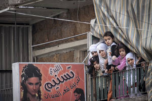 photo - In this Friday, Nov. 30, 2012 photo, Syrian women and children watch a demonstration after Friday prayers in the Bustan Al-Qasr district of Aleppo, Syria. After months of fighting, thousands of residents have returned to the city as they attempt to return to their daily lives while heavy fighting is still taking place along the front lines in the city. Public demonstrations have unfolded after several weeks of silence as residents demand an end to the violence in Aleppo. (AP Photo/Narciso Contreras)