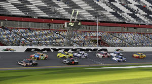 photo - Denny Hamlin (11) and Kyle Busch (18) lead a group of cars through the front stretch during practice for the NASCAR Sprint Unlimited Shootout auto race at Daytona International Speedway, Friday, Feb. 15, 2013, in Daytona Beach, Fla. (AP Photo/John Raoux)