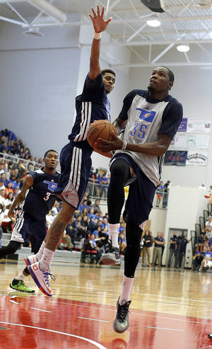 Photo - Oklahoma City's Kevin Durant (35) shoots a lay up as Jeremy Lamb (11) defends during the Oklahoma City Thunder's  Blue and White scrimmage at Westmoore High School in Moore, Okla., Sunday, Oct. 13, 2013. Photo by Sarah Phipps, The Oklahoman