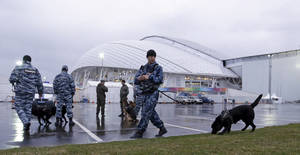 Photo - Security personnel walk with their dogs outside Fisht Olympic Stadium at the 2014 Winter Olympics Monday, Jan. 27, 2014, in Sochi, Russia. The Olympics begin Feb. 7th. (AP Photo/David J. Phillip)