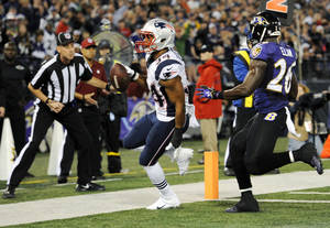 Photo - New England Patriots running back Shane Vereen, left, runs past Baltimore Ravens free safety Matt Elam for a touchdown in the first half of an NFL football game, Sunday, Dec. 22, 2013, in Baltimore. (AP Photo/Nick Wass)