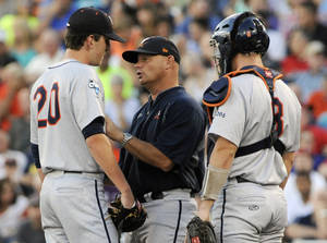 Photo - Virginia coach Brian O'Connor talks to pitcher Brandon Waddell (20) in the fourth inning of Game 2 of the best-of-three NCAA baseball College World Series finals against Vanderbilt in Omaha, Neb., Tuesday, June 24, 2014. At right is catcher Robbie Coman (8). (AP Photo/Eric Francis)