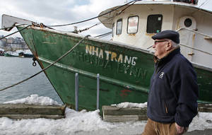 Photo - In this photo taken Wednesday, Feb. 13, 2013, Ron Gilson, a 79-year-old life Gloucester native, walks along the fish pier in Gloucester, Mass. In Gilson's life he's worked throughout the fishing industry from working on the wharf in his youth to a historian on Gloucester in his later life. In May, a massive reduction is coming to the catch limit for cod caught in the Gulf of Maine, just outside Gloucester Harbor, and the cuts are acknowledged by fishermen, regulators and environmentalists to be devastating, and perhaps fatal, for the historic industry. (AP Photo/Charles Krupa)