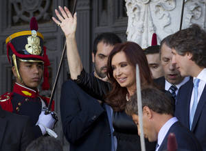 Photo - Argentina's President Cristina Fernandez, center, waves to supporters as she leaves the Argentine National Congress where she inaugurated the opening legislative session, in Buenos Aires, Argentina, Friday, March 1, 2013. Vice President Amado Boudou is pictured on far right. (AP Photo/Victor R. Caivano)