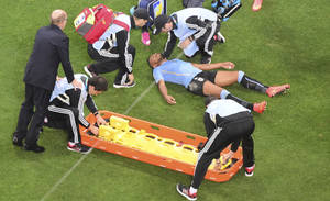 Photo - Uruguay's Alvaro Pereira is put on a stretcher during the group D World Cup soccer match between Uruguay and England at the Itaquerao Stadium in Sao Paulo, Brazil, Thursday, June 19, 2014.  (AP Photo/Francois Xavier Marit, pool)