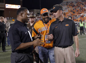 Photo - Oklahoma State quarterback Mike Gundy talks with Barry Sanders following a college football game between the Oklahoma State University Cowboys (OSU) and the University of Kansas Jayhawks (KU) at Boone Pickens Stadium in Stillwater, Okla., Saturday, Nov. 9, 2013. Photo by Sarah Phipps, The Oklahoman