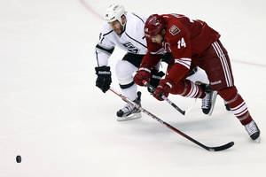 Photo -   Phoenix Coyotes left wing Taylor Pyatt (14) and Los Angeles Kings left wing Dwight King (74) battle for the puck during the second period of Game 5 of the NHL hockey Stanley Cup Western Conference finals, Tuesday, May 22, 2012, in Glendale, Ariz. (AP Photo/Matt York)