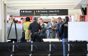 Photo - FILE - In this Nov. 1, 2013 file photo, federal and local investigators gather in Terminal 3 at Los Angeles International Airport where a gunman armed with a semi-automatic rifle opened fire, killing a Transportation Security Administration employee and wounding two other people. Two armed police officers, not seen in this photo, assigned to guard the terminal, left for breaks without informing dispatchers as required minutes before the gunfire erupted. (AP Photo/Ringo H.W. Chiu, File)