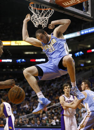 photo - Denver Nuggets' Kosta Koufos (41) dunks against the Phoenix Suns during the first half of an NBA basketball game, Monday, March 11, 2013, in Phoenix. (AP Photo/Matt York)