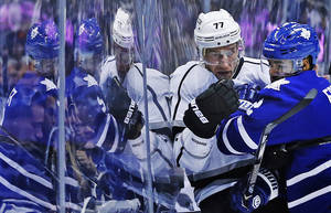 Photo - Toronto Maple Leafs' Mark Fraser, left, collides with Los Angeles Kings' Jeff Carter  againsty the glass during first period NHL hockey action in Toronto, Wednesday, Dec. 11, 2013.(AP Photo/The Canadian Press, Mark Blinch)