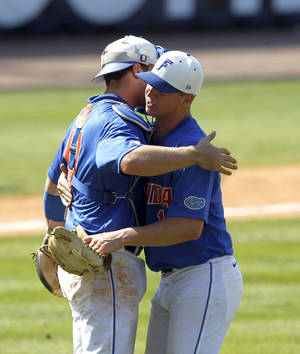 Photo - Florida's Taylor Gushue, left, celebrates with Bobby Poyner, right, after they defeated South Carolina, 7-2,  at the Southeastern Conference NCAA college baseball tournament on Thursday, May 22, 2014, in Hoover, Ala. (AP Photo/Butch Dill)