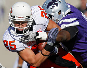 Photo - Oklahoma State's Josh Cooper (25) is hit by after a reception by a member of the Kansas State defense during the first half of the college football game between the Oklahoma State University Cowboys (OSU) and the Kansas State University Wildcats (KSU) on Saturday, Oct. 30, 2010, in Manhattan, Kan.   Photo by Chris Landsberger, The Oklahoman