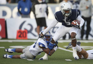 Photo - Nevada's Nigel Westbrooks (3) attempts to break a tackle from Air Force's Kalon Baker (28) during the first half of an NCAA college football game in Reno, Nev., on Saturday, Sept. 28, 2013. (AP Photo/Cathleen Allison)