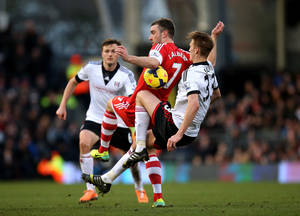 Photo - Southampton's Rickie Lambert, center, battles for possession of the ball with Fulham's Dan Burn, right, during their English Premier League soccer match at Craven Cottage, London, Saturday, Feb. 1, 2014. (AP Photo/John Walton, PA Wire)   UNITED KINGDOM OUT   -   NO SALES   -   NO ARCHIVES