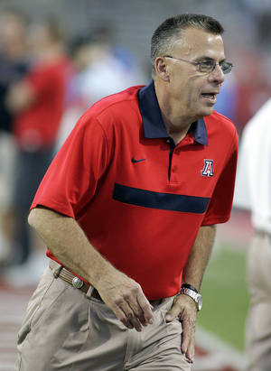 Photo - University of Arizona's new football coach, Tim Kish, runs off the field as before an NCAA college football game between Arizona and UCLA at Arizona Stadium in Tucson, Ariz., Thursday, Oct. 20, 2011. (AP Photo/John Miller) ORG XMIT: AZJM101