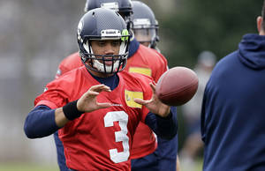 Photo - Seattle Seahawks quarterback Russell Wilson reaches for the ball during NFL football practice Thursday, Jan. 16, 2014, in Renton, Wash. The Seahawks play the San Francisco 49ers on Sunday in the NFC championship game. (AP Photo/Elaine Thompson)
