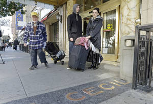 Photo - A man, left, leaves the Cecil Hotel with belongings as Michael and Sabina Baugh, both 27, of Plymouth, England, wait for transportation as they leave the hotel in downtown Los Angeles Wednesday, Feb. 20, 2013.  Early Tuesday, police discovered the body of a Canadian woman at the bottom of the historic hotel's water tank, weeks after she was reported missing.  The Baughs, on a 14-day tour package, had been there eight days and had showered in and drank the water. The couple's tour operator was less than cooperative in finding them other accommodations.  (AP Photo/Reed Saxon)