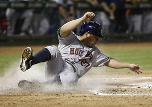 Photo - Houston Astros' Jose Altuve (27) slides across home plate scoring on a single by Astros' Chris Carter off Texas Rangers starting pitcher Martin Perez during the fourth inning of a baseball game, Wednesday, Sept. 25, 2013, in Arlington, Texas. (AP Photo/Jim Cowsert)
