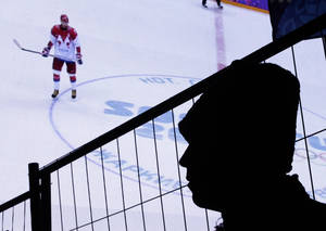 Photo - A Russian policeman watches a men's ice hockey match between USA and Russia on a large video screen at an entertainment venue associated with the 2014 Winter Olympics, Saturday, Feb. 15, 2014, in Krasnaya Polyana, Russia. (AP Photo/Charlie Riedel)