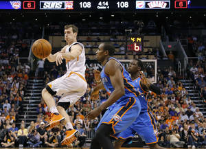 Photo - Phoenix Suns guard Goran Dragic (1), of Slovenia, dishes off as Oklahoma City Thunder forward Serge Ibaka, right, of Congo, defends, during the first half of an NBA basketball game on Sunday, April 6, 2014, in Phoenix. The Suns won 122-115. (AP Photo/Matt York)