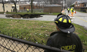 Photo - Officials survey a gaping sinkhole that opened up a residential street on Chicago's South Side after a cast iron water main dating back to 1915 broke during a massive rain storm, Thursday, April 18, 2013, in Chicago. The hole spanned the entire width of the road and chewed up grassy areas abutting the sidewalk. Two of the cars that disappeared inside had been parked, but a third was being driven when the road buckled and caved in. Only the hood of one of the vehicles can be seen peeking from the chasm.(AP Photo/M. Spencer Green)