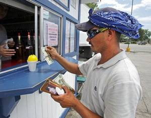 Photo - Paving company employee Omar Ibarra buys a sno cone from Eskimo Sno on Lindsey Street in 100 degree heat on this week. <strong>STEVE SISNEY - THE OKLAHOMAN</strong>